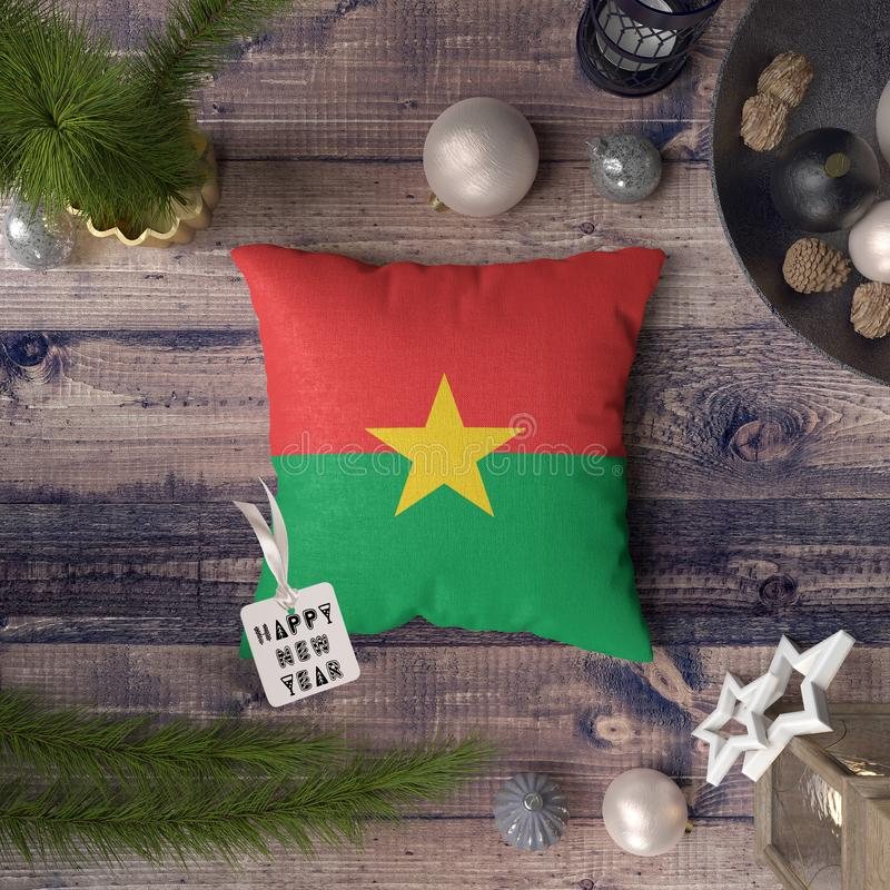 Happy New Year tag with Burkina flag on pillow. Christmas decoration concept on wooden table with lovely objects.  stock photography