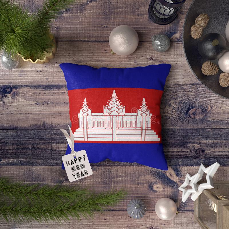 Happy New Year tag with Cambodia flag on pillow. Christmas decoration concept on wooden table with lovely objects.  royalty free stock image