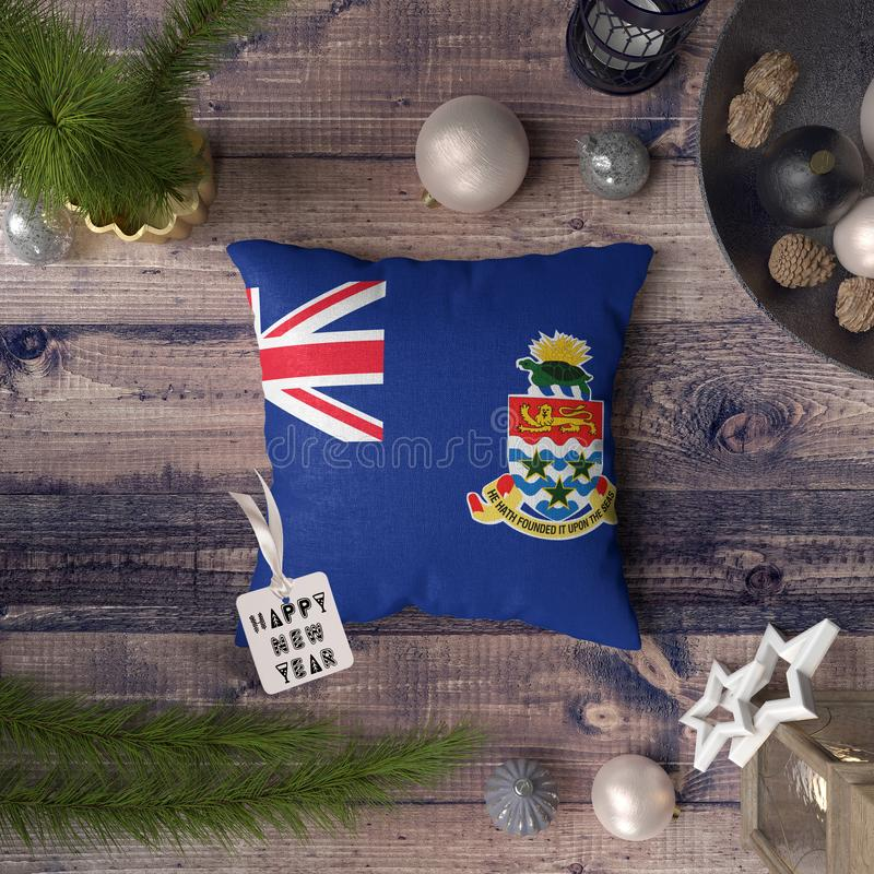 Happy New Year tag with Cayman Islands flag on pillow. Christmas decoration concept on wooden table with lovely objects.  royalty free stock photography