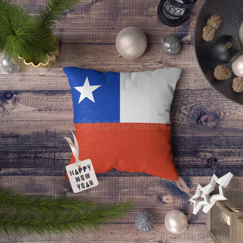 Happy New Year tag with Chile flag on pillow. Christmas decoration concept on wooden table with lovely objects.  royalty free stock photography