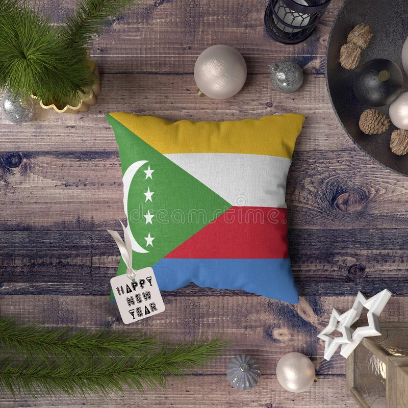 Happy New Year tag with Comoros flag on pillow. Christmas decoration concept on wooden table with lovely objects.  royalty free stock photo