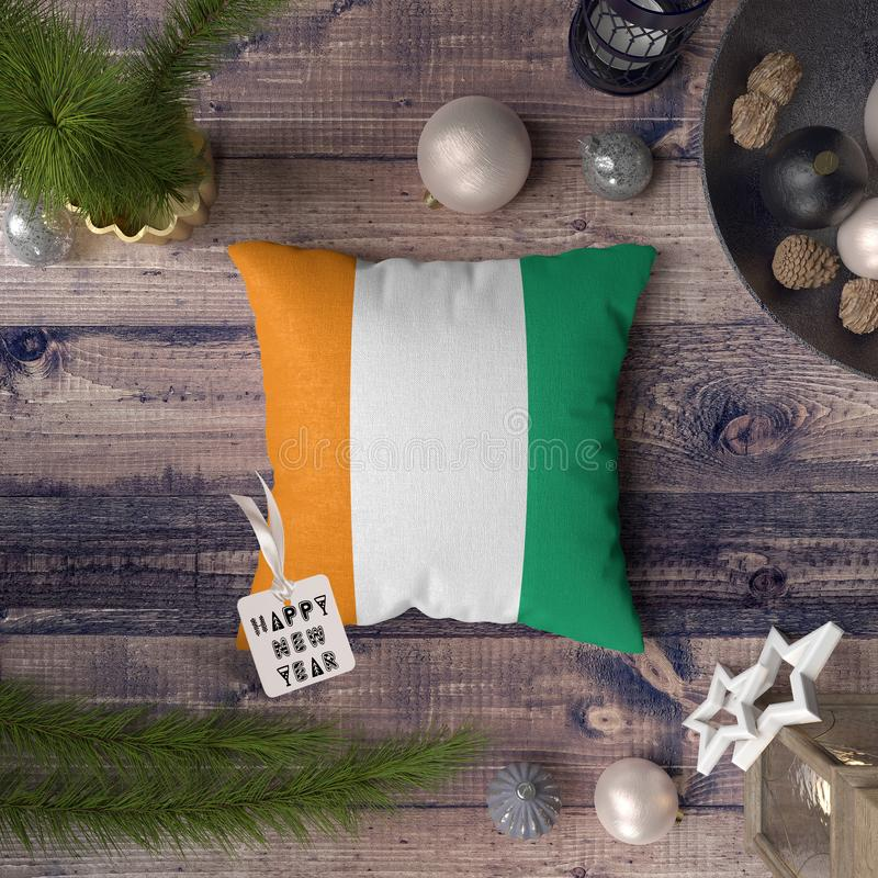 Happy New Year tag with Cote D`ivoire flag on pillow. Christmas decoration concept on wooden table with lovely objects.  stock images