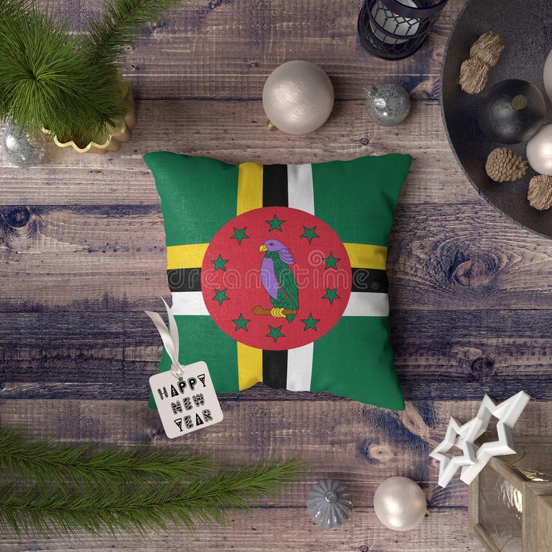 Happy New Year tag with Dominica flag on pillow. Christmas decoration concept on wooden table with lovely objects.  royalty free stock image