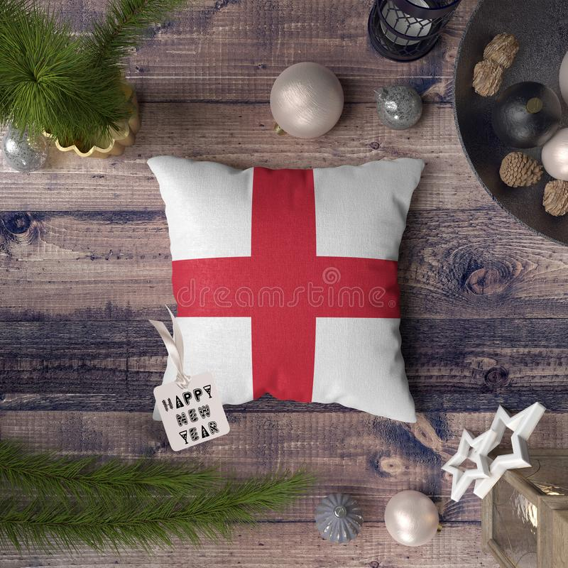 Happy New Year tag with England flag on pillow. Christmas decoration concept on wooden table with lovely objects.  royalty free stock photography
