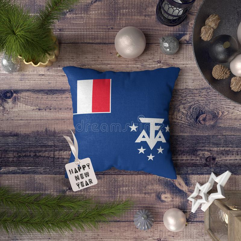 Happy New Year tag with French Southern and Antarctic Lands flag on pillow. Christmas decoration concept on wooden table with. Lovely objects royalty free stock photo