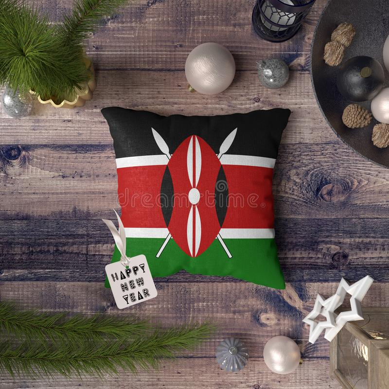 Happy New Year tag with Kenya flag on pillow. Christmas decoration concept on wooden table with lovely objects.  royalty free stock image