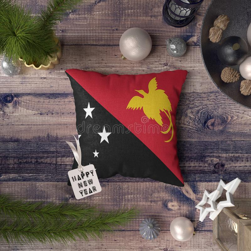 Happy New Year tag with Papua New Guinea flag on pillow. Christmas decoration concept on wooden table with lovely objects stock image