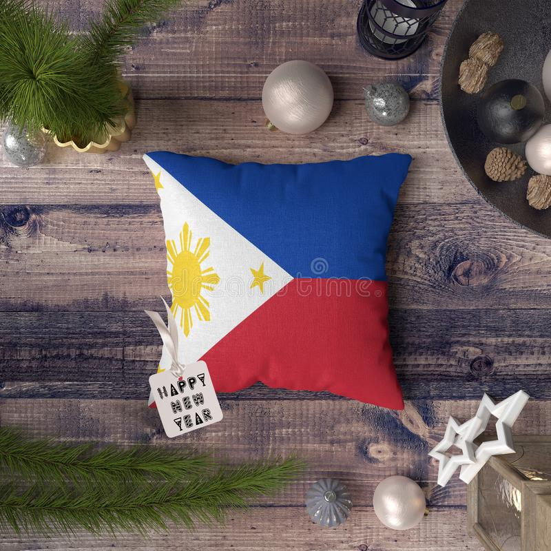 Happy New Year tag with Philippines flag on pillow. Christmas decoration concept on wooden table with lovely objects.  royalty free stock images