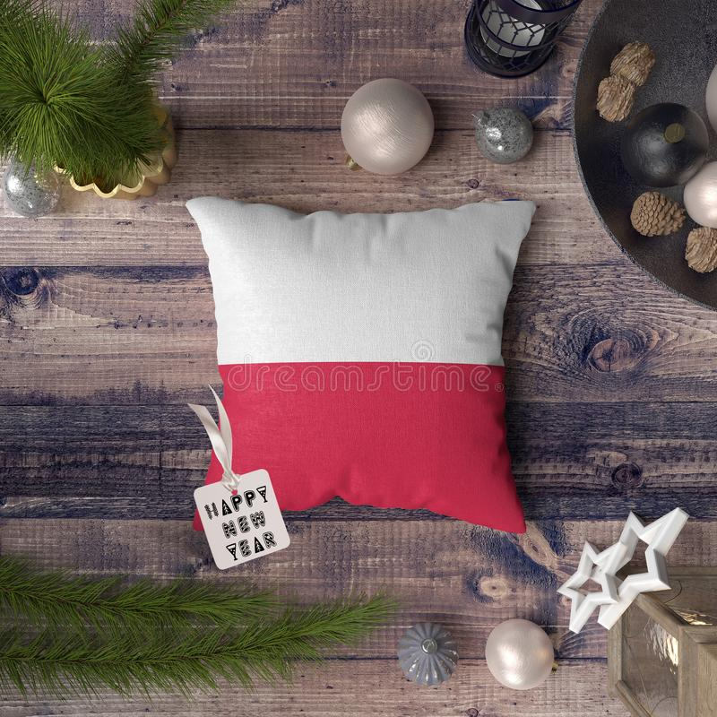 Happy New Year tag with Poland flag on pillow. Christmas decoration concept on wooden table with lovely objects royalty free stock image