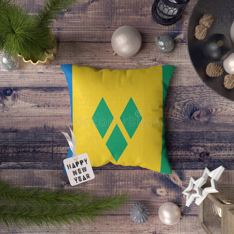 Happy New Year tag with Saint Vincent and the Grenadines flag on pillow. Christmas decoration concept on wooden table with lovely vector illustration