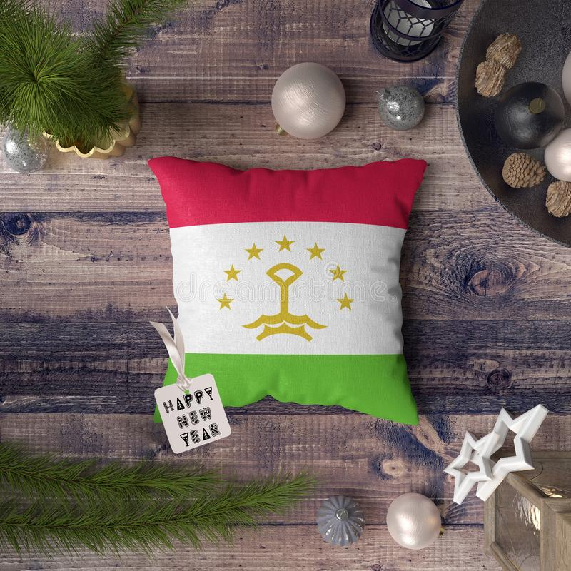 Happy New Year tag with Tajikistan flag on pillow. Christmas decoration concept on wooden table with lovely objects.  royalty free stock photos