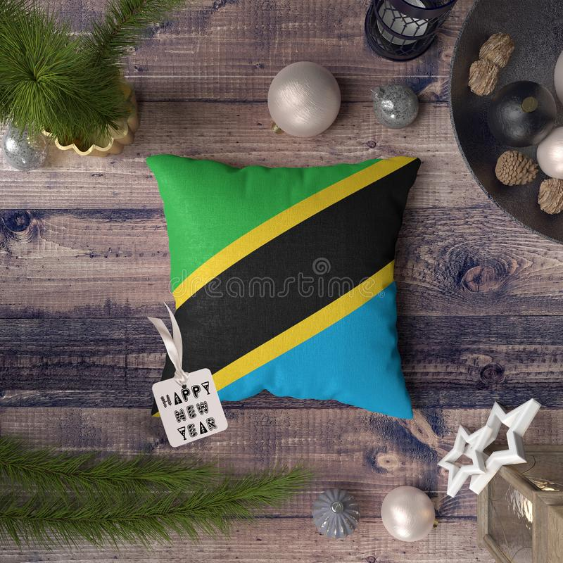 Happy New Year tag with Tanzania flag on pillow. Christmas decoration concept on wooden table with lovely objects.  royalty free stock images