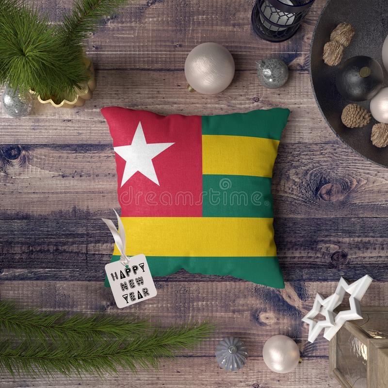 Happy New Year tag with Togo flag on pillow. Christmas decoration concept on wooden table with lovely objects.  stock image