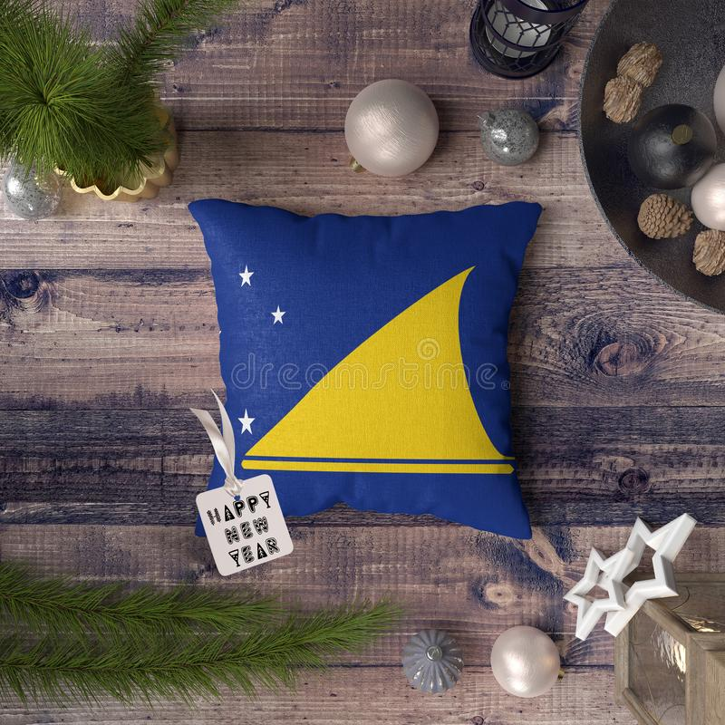 Happy New Year tag with Tokelau flag on pillow. Christmas decoration concept on wooden table with lovely objects.  royalty free stock image