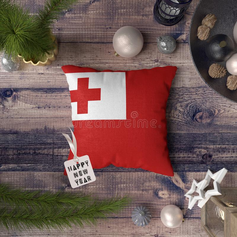 Happy New Year tag with Tonga flag on pillow. Christmas decoration concept on wooden table with lovely objects.  stock photography