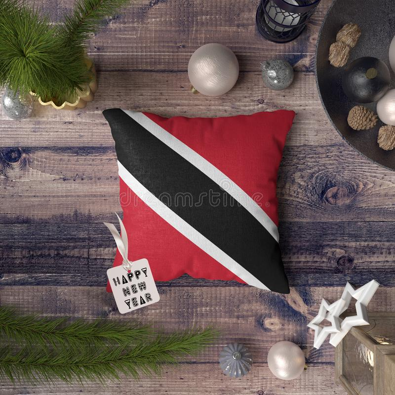 Happy New Year tag with Trinidad and Tobago flag on pillow. Christmas decoration concept on wooden table with lovely objects.  royalty free stock image