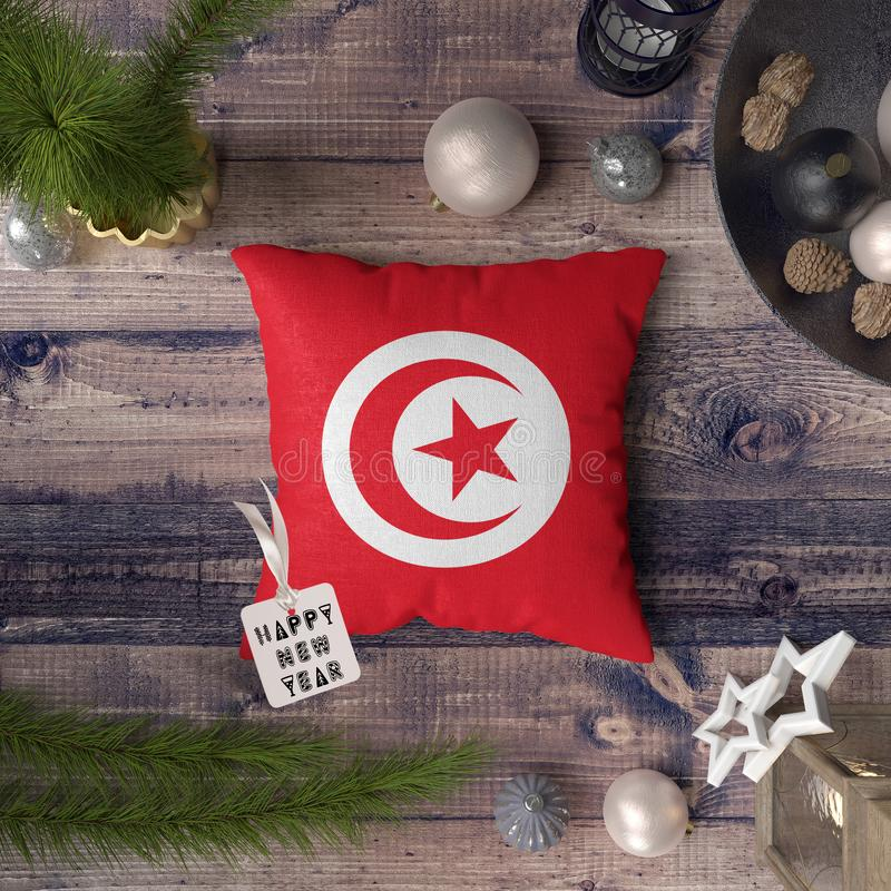 Happy New Year tag with Tunisia flag on pillow. Christmas decoration concept on wooden table with lovely objects.  royalty free stock photography