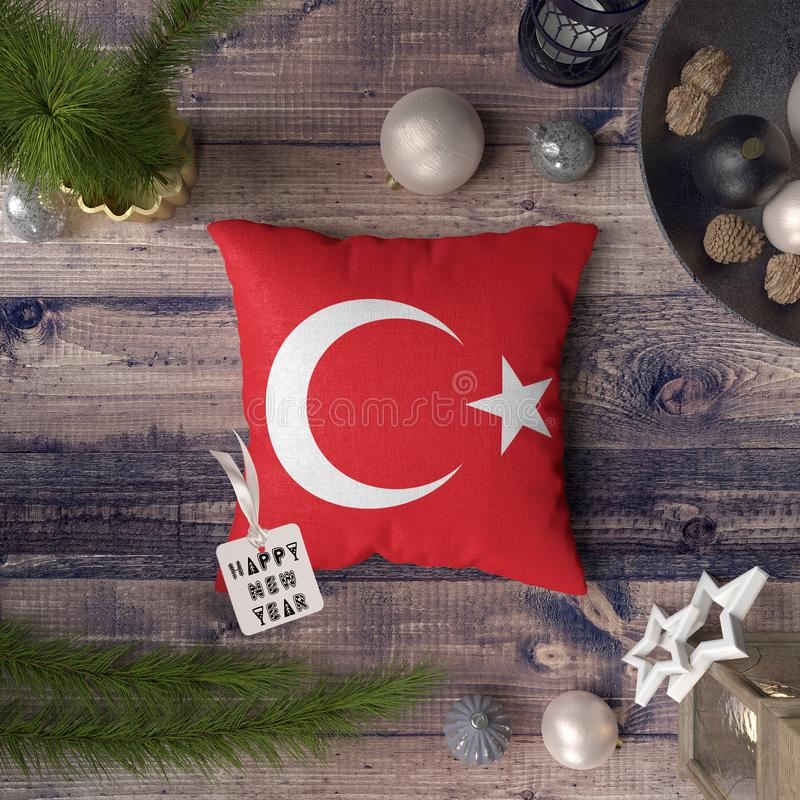 Happy New Year tag with Turkey flag on pillow. Christmas decoration concept on wooden table with lovely objects.  royalty free stock image