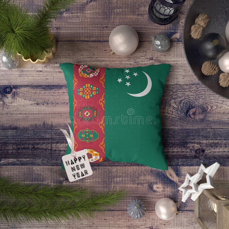 Happy New Year tag with Turkmenistan flag on pillow. Christmas decoration concept on wooden table with lovely objects.  stock image
