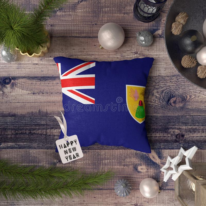 Happy New Year tag with Turks and Caicos Islands flag on pillow. Christmas decoration concept on wooden table with lovely objects.  royalty free stock images