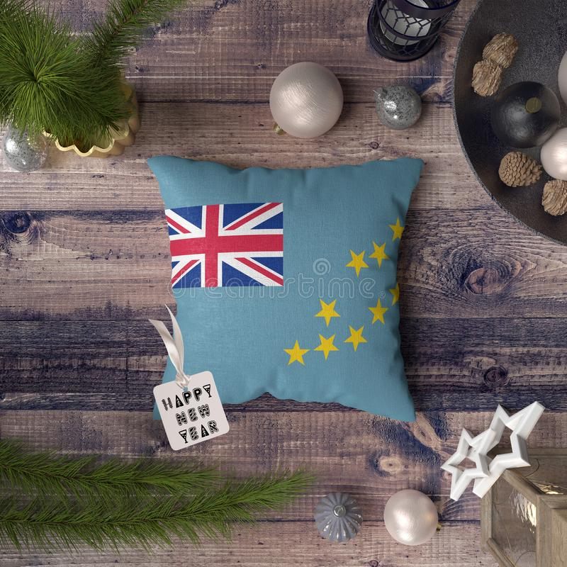 Happy New Year tag with Tuvalu flag on pillow. Christmas decoration concept on wooden table with lovely objects.  stock photography