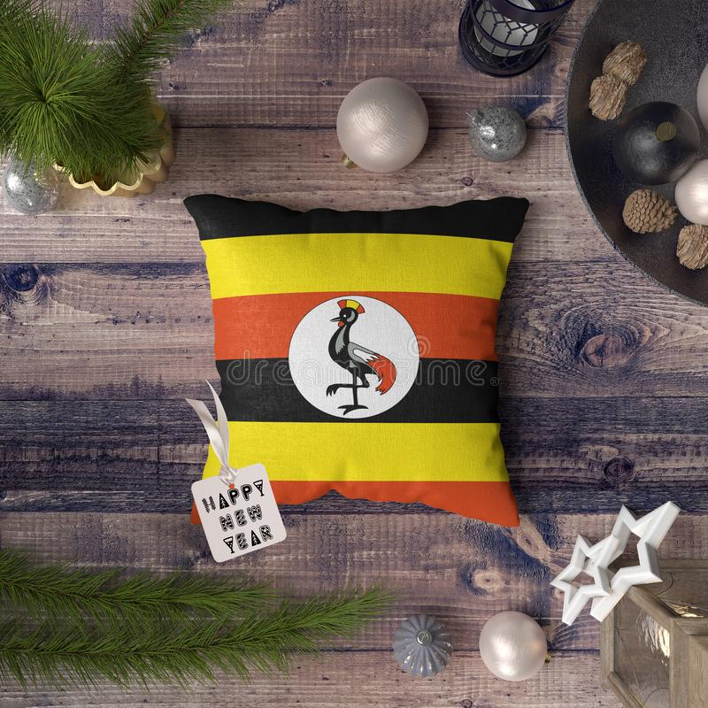 Happy New Year tag with Uganda flag on pillow. Christmas decoration concept on wooden table with lovely objects.  royalty free stock photo