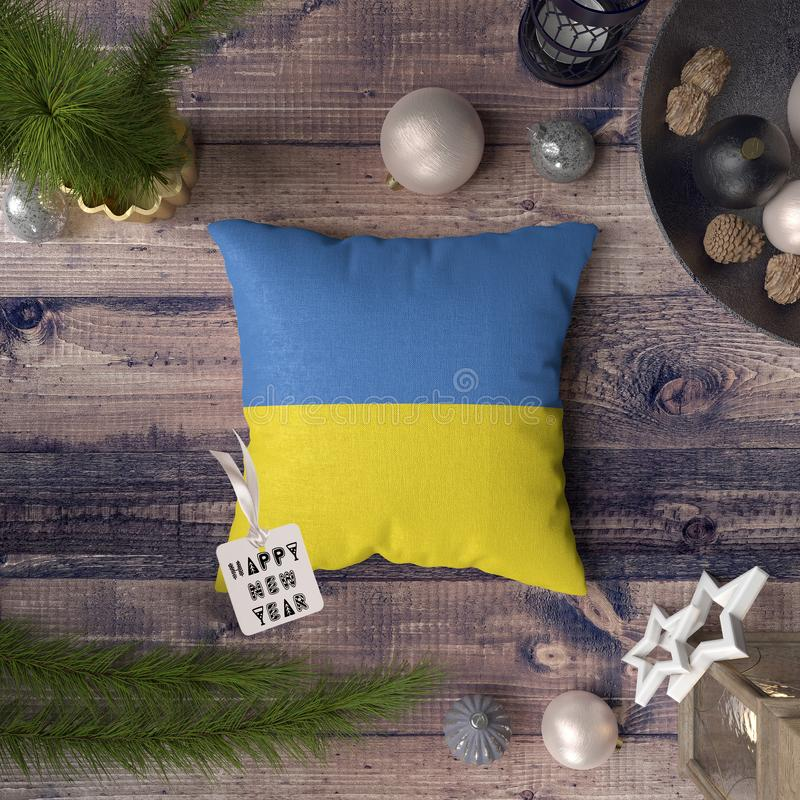 Happy New Year tag with Ukraine flag on pillow. Christmas decoration concept on wooden table with lovely objects.  royalty free stock photos