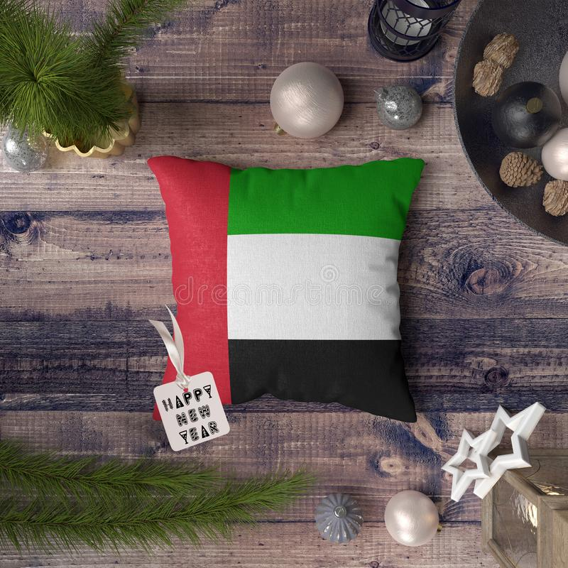 Happy New Year tag with United Arab Emirates flag on pillow. Christmas decoration concept on wooden table with lovely objects.  stock photo