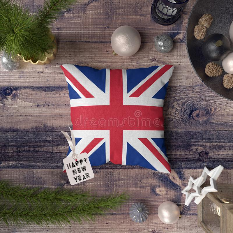 Happy New Year tag with United Kingdom flag on pillow. Christmas decoration concept on wooden table with lovely objects.  royalty free stock images