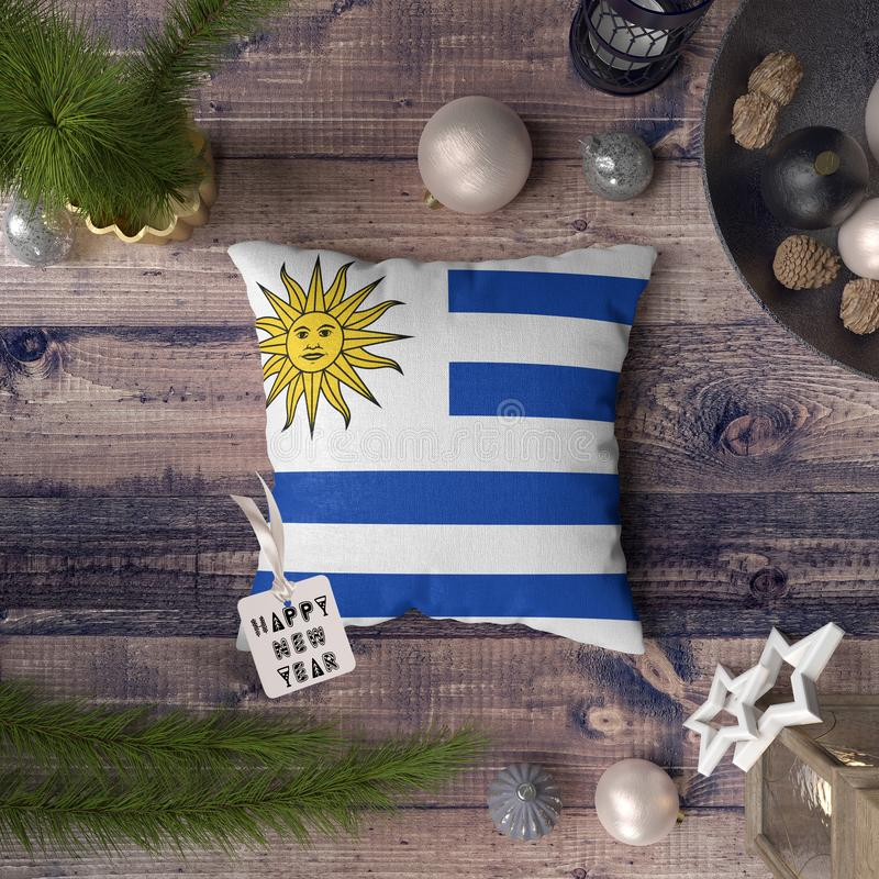Happy New Year tag with Uruguay flag on pillow. Christmas decoration concept on wooden table with lovely objects.  royalty free stock photo
