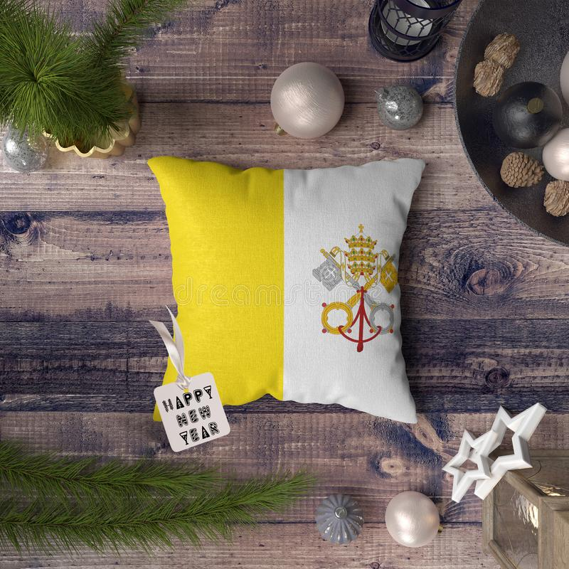 Happy New Year tag with Vatican City Holy See flag on pillow. Christmas decoration concept on wooden table with lovely objects.  royalty free stock photography