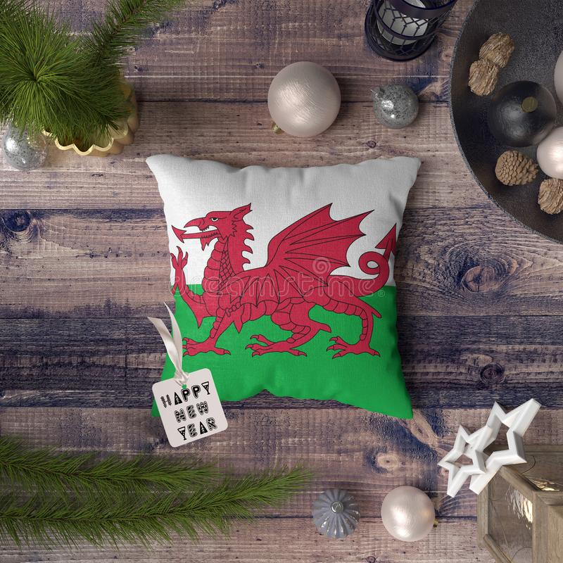 Happy New Year tag with Wales flag on pillow. Christmas decoration concept on wooden table with lovely objects.  royalty free stock photography