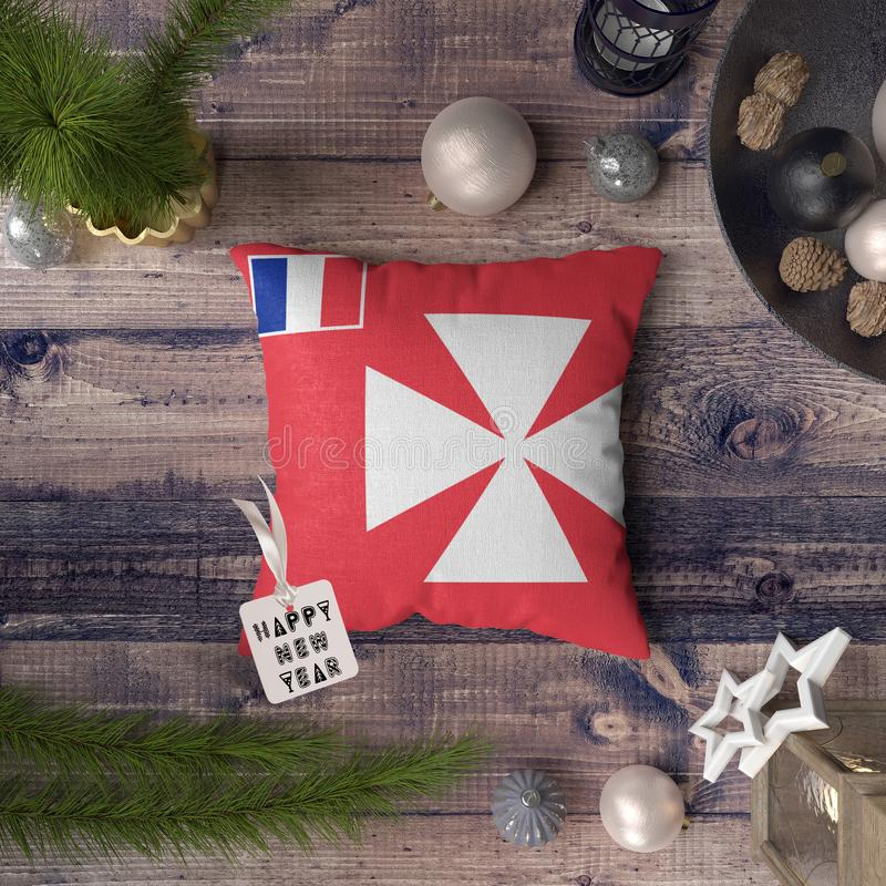 Happy New Year tag with Wallis and Futuna flag on pillow. Christmas decoration concept on wooden table with lovely objects.  royalty free stock photo