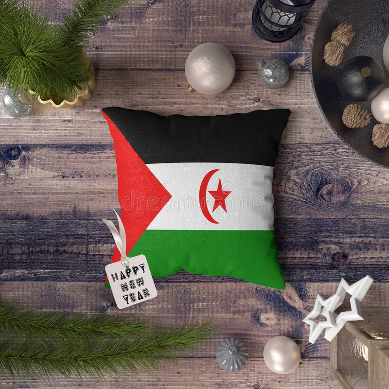 Happy New Year tag with Western Sahara flag on pillow. Christmas decoration concept on wooden table with lovely objects.  royalty free stock photo