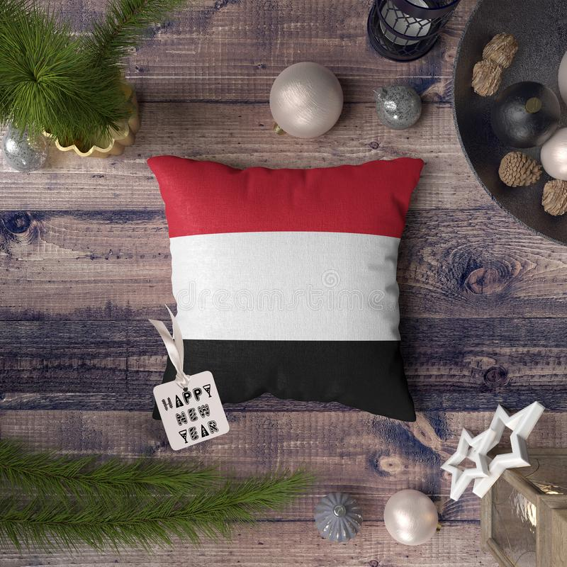 Happy New Year tag with Yemen flag on pillow. Christmas decoration concept on wooden table with lovely objects.  royalty free stock photography