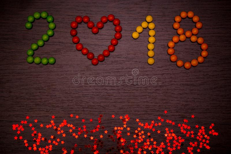 Happy new year 2018 text from colorful candies on wooden background stock photography