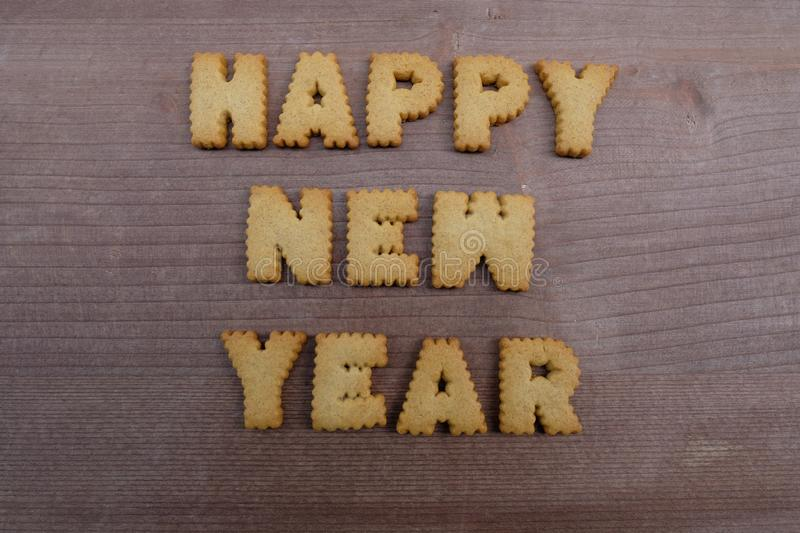 Happy New Year text composed with biscuit letters over a wooden board stock image