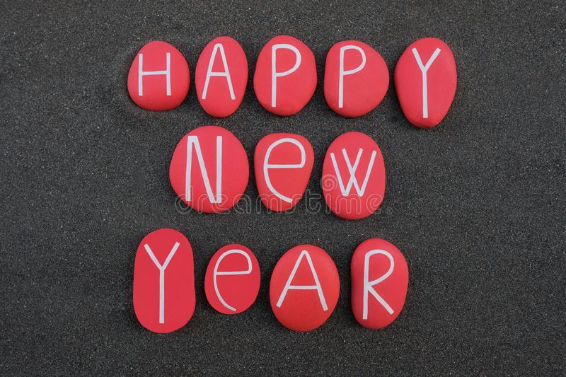 Happy New Year text composed with red colored stone letters over black volcanic sand royalty free illustration