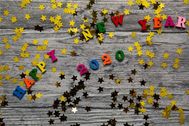 2020 Happy New year text for greeting card, with gold stars and colored letters on wooden background, calendar, invitation royalty free stock images