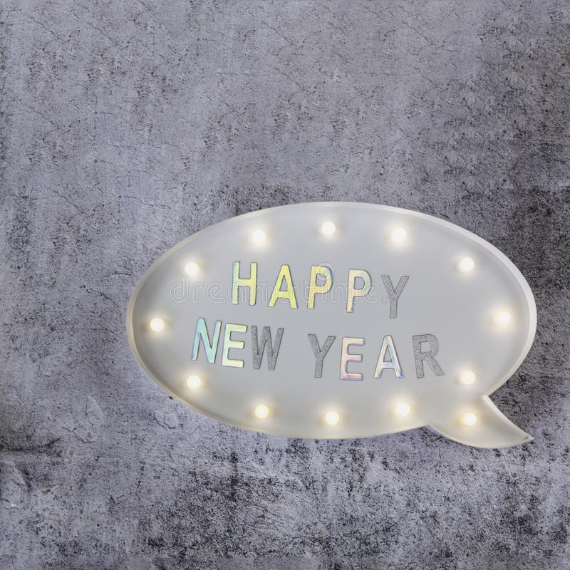 Happy New Year text in lightbox on grey minimalistic background. Copy space stock photos