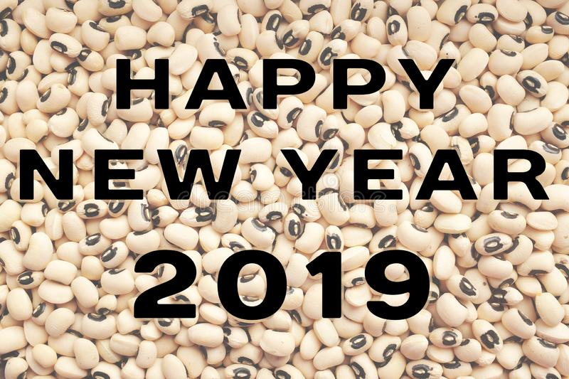 Happy New Year 2019 text over black eyed peas. HAPPY NEW YEAR 2019 text over a dried black eyed beans background, traditional food considered to bring prosperity royalty free stock image
