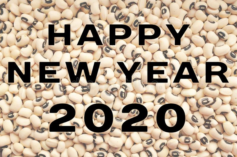 Happy New Year 2020 text over black eyed peas. HAPPY NEW YEAR 2020 text over a dried black eyed beans background, traditional food considered to bring prosperity royalty free stock images