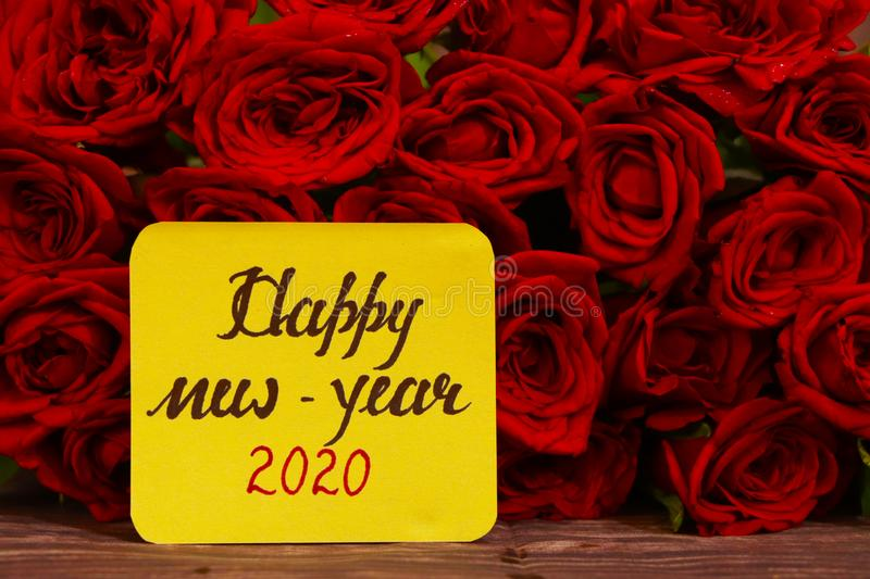 Happy New Year 2020 text with Red roses in a bunch as a background. stock photography