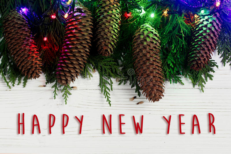 Happy new year text sign on christmas garland lights and pine co. Nes on fir branches. stylish white rustic wooden background. space for text. holiday greeting stock photo