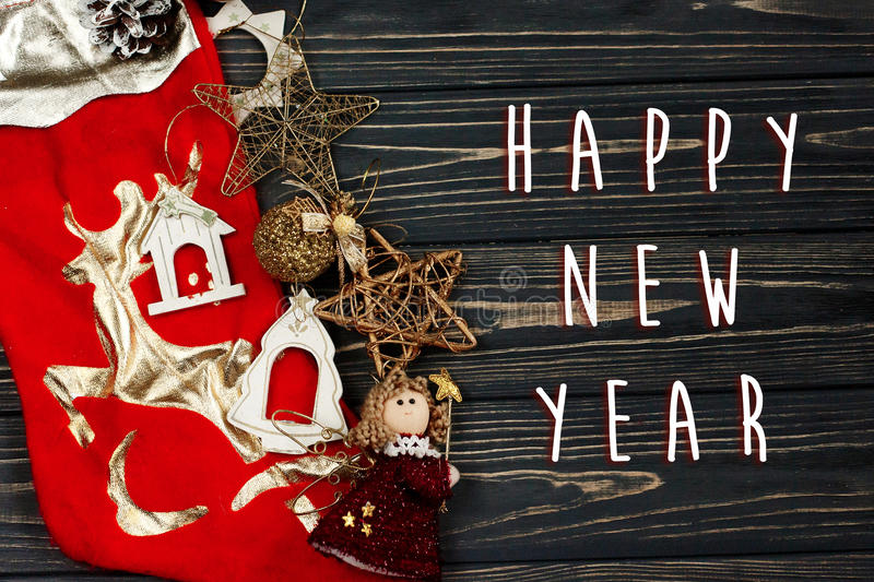 happy new year text sign on christmas golden stylish toys. ornament border on black rustic wooden background. space for text. royalty free stock image