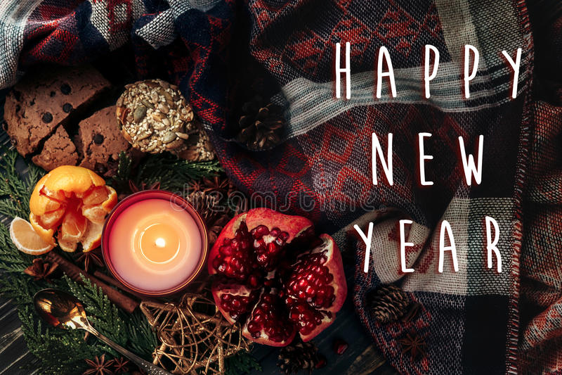 happy new year text sign on stylish christmas flat lay with candle and presents garnet cookies fruits on rustic wooden royalty free stock photo