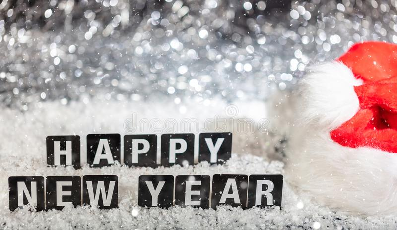 Happy new year text on snow, abstract bokeh lights background royalty free stock photography