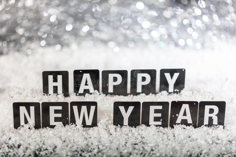 Happy new year text on snow, abstract bokeh lights background stock photos