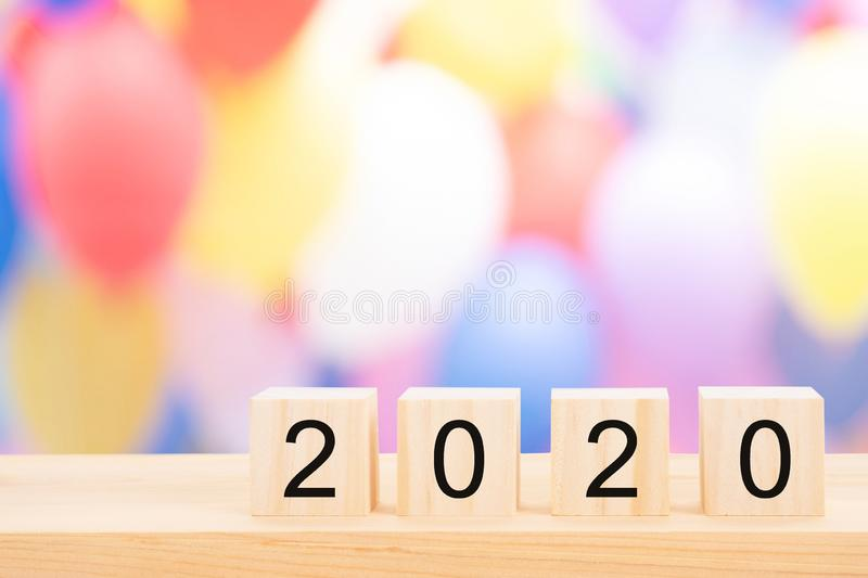 Happy new year 2020 text on wooden cubes on wooden pine table and blur light bokeh background. Banner with copy space for text royalty free stock images