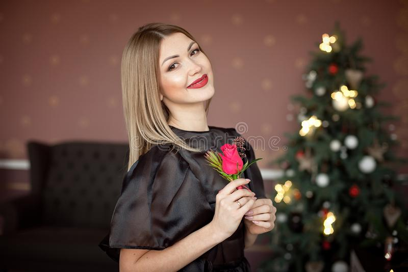Happy New Year to you.One beautiful young woman in a black dress and bright makeup celebrating Christmas on the. Background of New Year`s garlands. New Year stock images